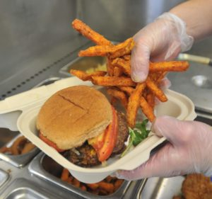 Morgan Feddersen puts together a vegie burger called a Franklin, with sweet potatoe fries at the Baby Berk food truck on the UMass campus.
